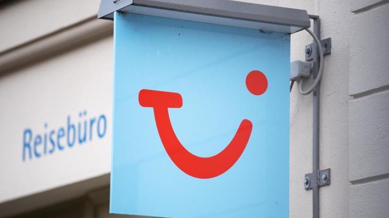 Das Logo des Reiseunternehmens TUI hängt neben einem Reisebüro in der Innenstadt. Foto: Soeren Stache/dpa/Archivbild