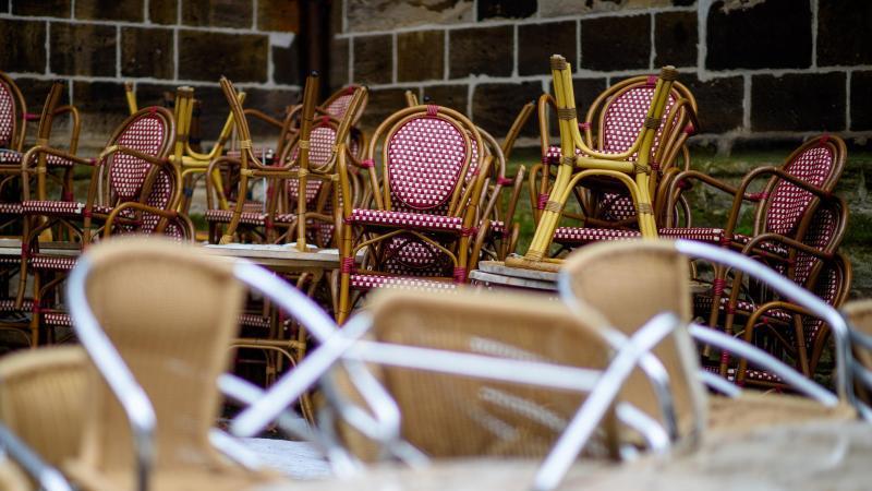 Stühle von Kaffees stehen in der Quedlinburger Altstadt am Straßenrand gestapelt. Foto: Klaus-Dietmar Gabbert/dpa-Zentralbild/dpa/Symbolbild