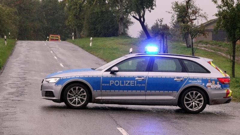 Ein Streifenwagen steht mit Blaulicht auf einerStraße. Foto: Harald Tittel/dpa/Symbolbild