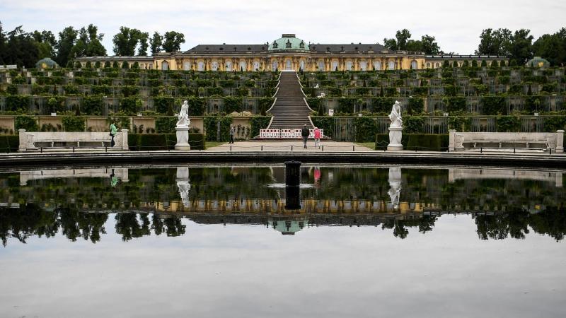 Besucher gehen durch den Park des Schlosses Sanssouci. Foto: Britta Pedersen/dpa-Zentralbild/ZB/Archivbild