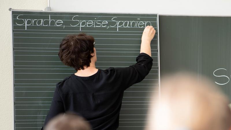 Eine Lehrerin schreibt in einer Grundschule Worte an eine Tafel. Foto: Sebastian Gollnow/dpa/Symbolbild