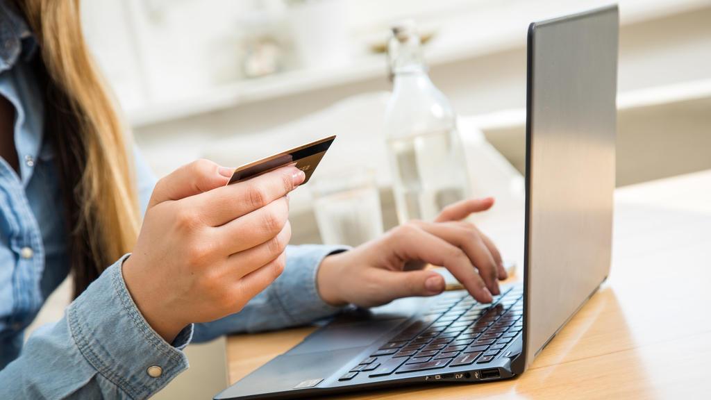 ARCHIV - 01.10.2020, Brandenburg, Wittenberge: Eine Frau tippt die Nummer ihrer Kreditkarte in ein Laptop. Viele Verbraucher zahlen ihre Einkäufe im Internet per Kreditkarte. Ab 2021 gelten dafür strengere Sicherheitsanforderungen - spätestens vom 15