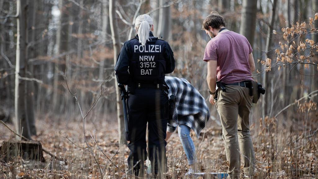 25.02.2021, Nordrhein-Westfalen, Köln: Polizeibeamte und Kriminalbeamte durchsuchen ein Waldstück im Stadtwald nach Spuren. Nach der Vergewaltigung einer Joggerin im Kölner Stadtwald befürchtet die Polizei eine Wiederholungstat. Darauf deute das atyp