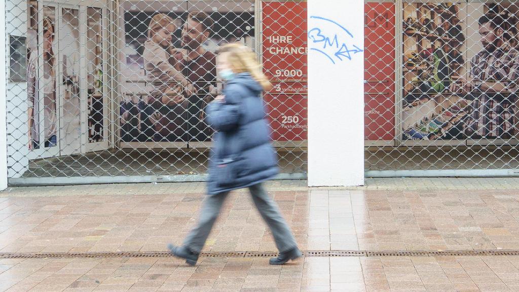 Die  Flensburger Innenstadt ist im Zuge der Coronavirus-Pandemie zum Hochinzidenzgebiet erklärt worden, man sieht eine einzige Frau, wie sie mit Mund-Nasen-Schutz-Maske an einem geschlossenen Laden vorbeigeht.
