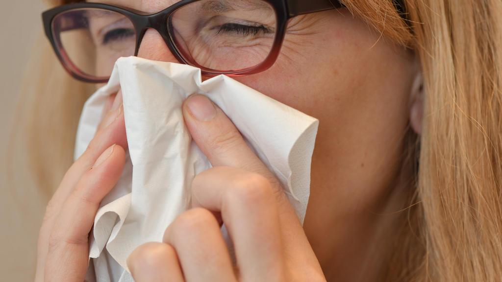 Eine Frau mit Brille benutzt ein Taschentuch. Die Maßnahmen zur Bekämpfung der Corona-Pandemie halten auch andere Infektionskrankheiten in Schach.