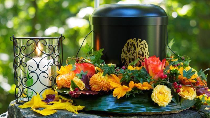 Eine für eine Bestattung vorbereitete Urne steht auf einem Friedhof. Foto: picture alliance / Nicolas Armer/dpa/Symbolbild