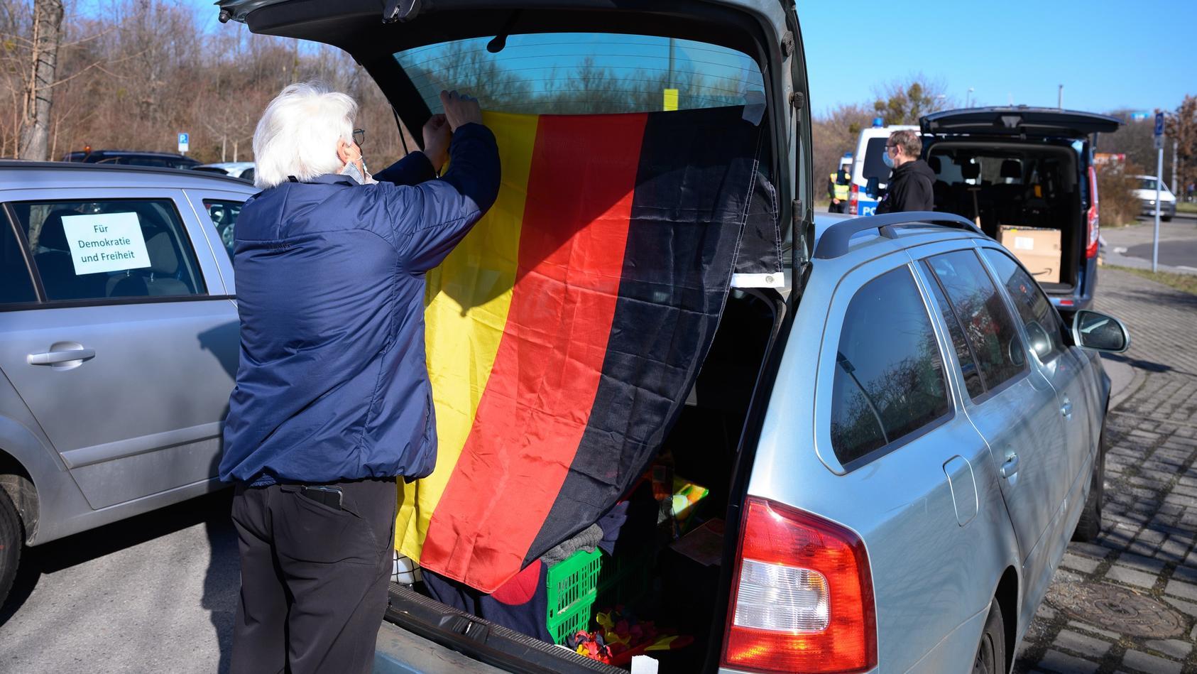 Ein Demonstrant bringt eine Deutschland-Flagge an sein Auto an.