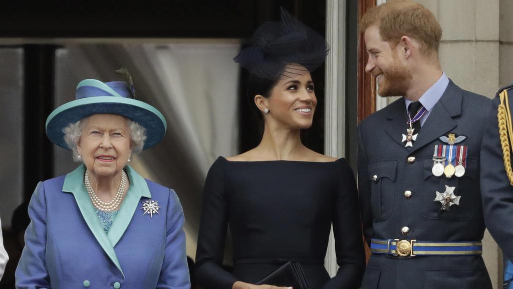 ARCHIV - 10.07.2018, Großbritannien, London: Die britische Königin Elizabeth II., ihr Enkel, Prinz Harry und seine Frau, Herzogin Meghan stehen während einer Flugschau der Royal Air Force auf einem Balkon des Buckingham-Palastes. (zu dpa Bericht: Que