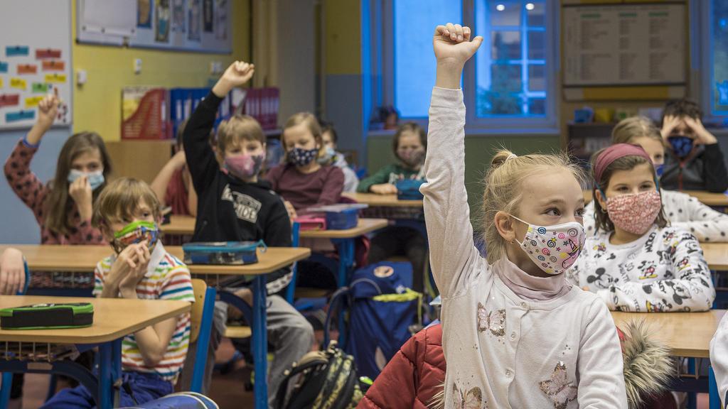 30.11.2020, Tschechien, Liberec: Schülerinnen und Schüler der Grundrunde Husova sitzen in einem Klassenraum und nehmen mit Gesichtsmasken am Unterricht teil. In Tschechien kehren in der Corona-Pandmie Schüler der dritten, vierten, fünften und neunten
