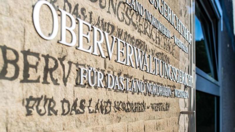 An der Aussenfassade am OVG hängt eine Hinweistafel mit dem Landeswappen von NRW und Schriftzügen. Foto: Guido Kirchner/dpa/Archivbild