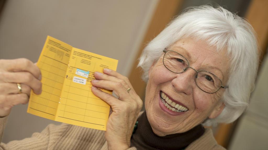 23.01.2021, Baden-Württemberg, Ulm: Seniorin Ursula Neuberger hält ihren Impfpass, in dem eine Grippe-Impfung (oben) und ihre erste Corona-Impfung vermerkt sind. Die meisten Menschen über 80 Jahre leben in Deutschland zu Hause. Sie müssen sich selbst