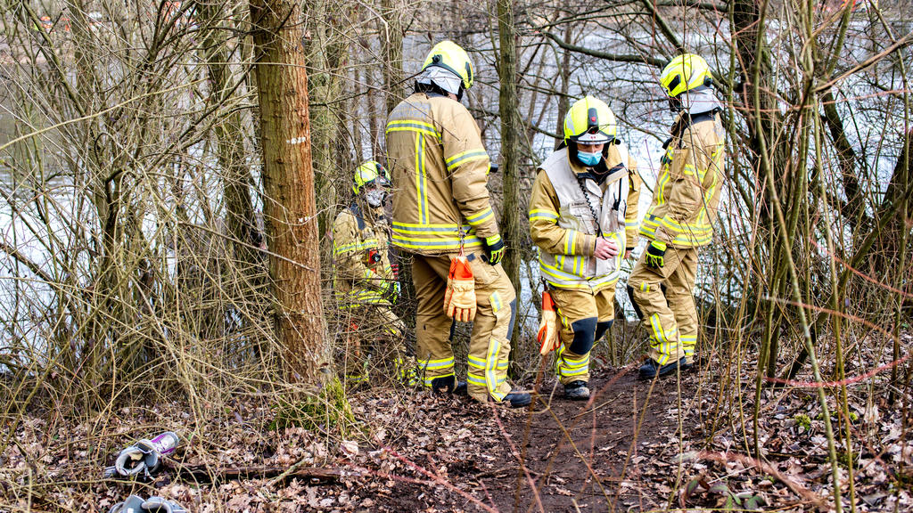 14.03.2021, Niedersachsen, Hannover: Einsatzkräfte der Feuerwehr stehen am Laher Teich, einem Baggersee im Nordosten der Stadt. Zwei Jungen im Alter von acht und neun Jahren waren in dem Gewässer ertrunken, nachdem sie einen ins Wasser gefallenen Bal
