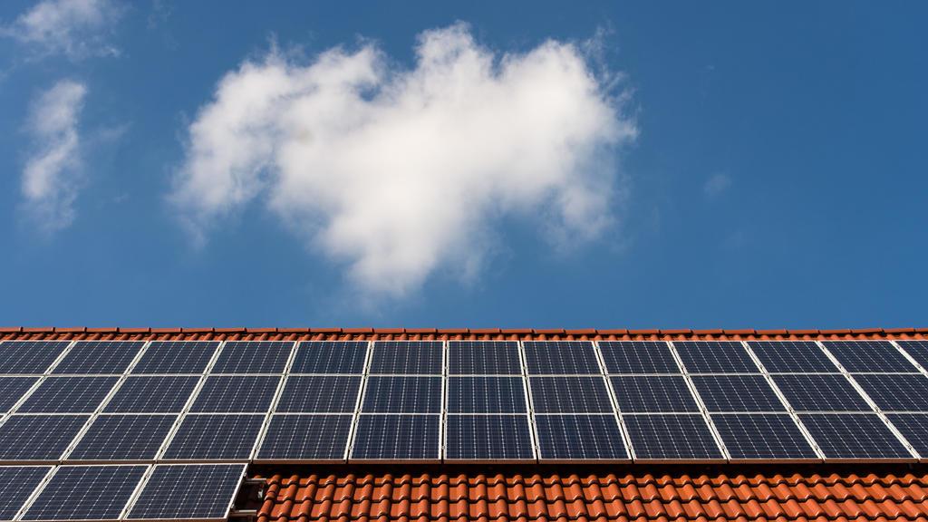 Solarzellen liegen auf einem Ziegeldach.