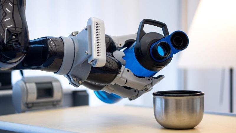 Ein Roboterarm gießt bei einem Versuchsaufbau am Deutschen Forschungszentrum für Künstliche Intelligenz Wasser in einen Becher. Foto: Sina Schuldt/dpa/Archivbild