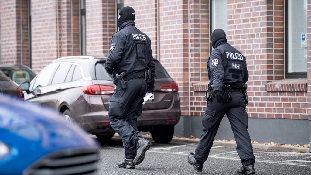 18.03.2021, Bremen: Polizisten gehen vor einem Gebäude im Stadtteil Hemelingen. Bei einem Großeinsatz im kriminellen Milieu in Bremen sind einem Medienbericht zufolge vier Menschen festgenommen worden. Hintergrund sei ein Ermittlungskomplex der Staat
