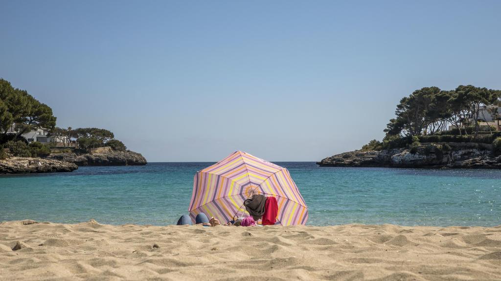 dpatopbilder - 25.03.2021, Spanien, Cala D'or: Zwei Personen liegen unter einem Sonnenschirm an einem Strand auf Mallorca. Angesichts der Corona-Pandemie sollen sich Flugpassagiere vor dem Start nach Deutschland künftig generell testen lassen müssen