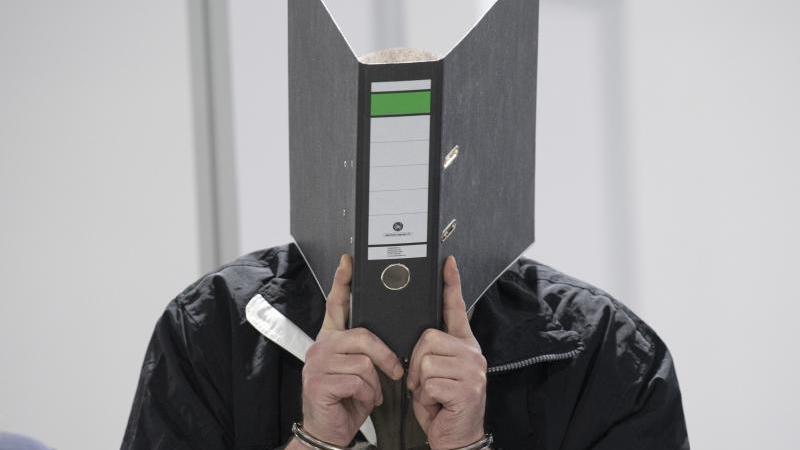 Mit Handschellen wird der Angeklagte in einen Verhandlungssaal vom Landgericht Wiesbaden geführt. Foto: Boris Roessler/dpa/Archivbild