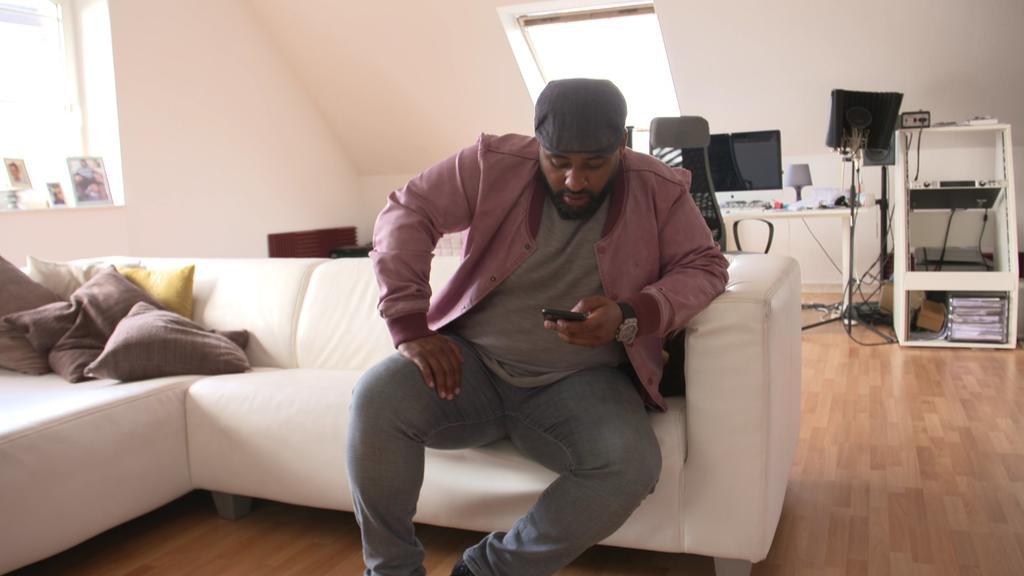 Ado Kojo schaut sich Reaktionen auf seinem Smartphone an