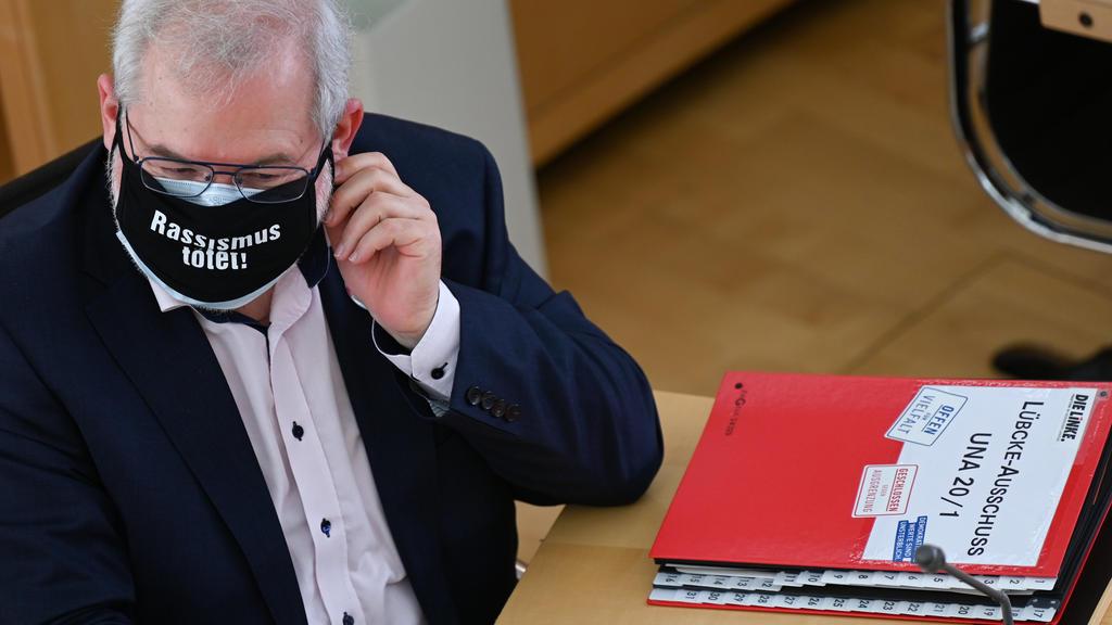 """31.03.2021, Hessen, Wiesbaden: Vor dem Abgeordneten Hermann Schaus (Die Linke), der eine schwarze Maske mit der Aufschrift """"Rassismus tötet"""" trägt, liegt zu Beginn der Sitzung des Lübcke-Untersuchungsausschusses im hessischen Landtag ein Aktenordner"""