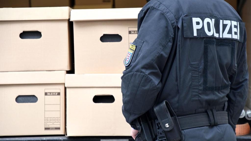ARCHIV - 20.01.2021, Hessen, Wiesbaden: Ein Polizeibeamter steht vor einem Lastwagen, der mit Kisten mit Aktenordnern beladen ist. Der Untersuchungsausschuss des hessischen Landtages zum Mordfall Lübcke hat wichtige Akten geliefert bekommen. (zu dpa