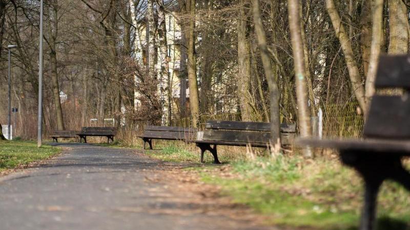 Die Sonne scheint auf leere Sitzbänke entlang eines Fußgängerweges. Foto: Nicolas Armer/dpa/Archivbild