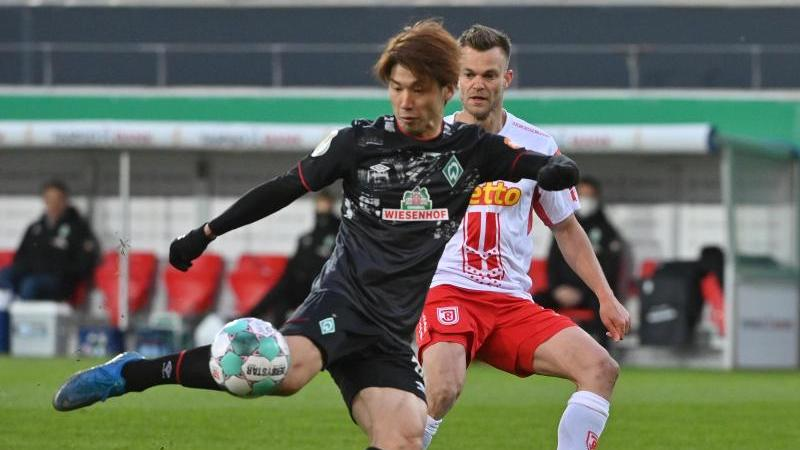 Bremens Yuya Osako (l) und Regensburgs Benedikt Saller in Aktion. Foto: Armin Weigel/dpa