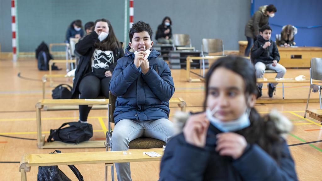 Schulkinder machen Corona-Schnelltest vor dem Unterricht in der Turnhalle.