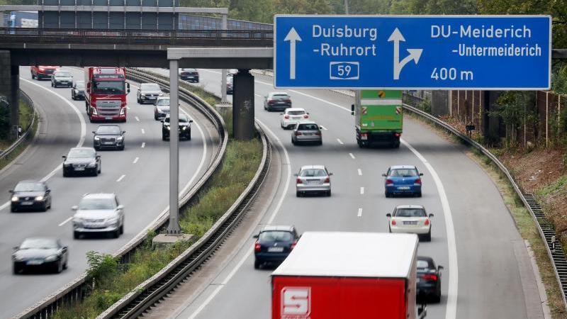 Autos fahren unter einem Autobahnschild auf der A59 durch. Foto: Roland Weihrauch/dpa/Archivbild