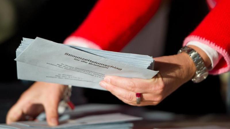 Wahlhelfer sortieren in einer Messehalle die Briefwahlstimmen zur Bundestagswahl. Foto: Inga Kjer/dpa/Archivbild