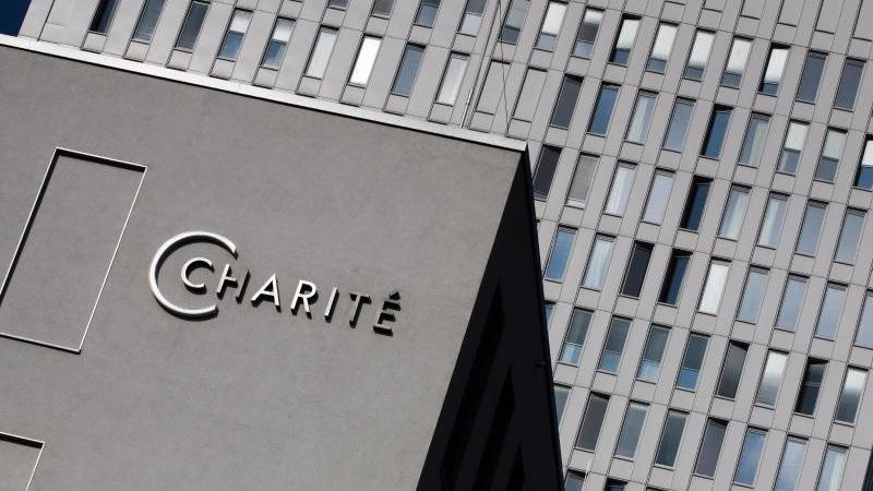 Das Bettenhochhaus der Berliner Charite ist hinter dem Charite-Logo an der Zentralen Notaufnahme zu sehen. Foto: Christoph Soeder/dpa/Archivbild