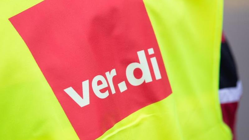 """Ein Demonstrant hat eine Warnweste mit der Aufschrift """"ver.di"""" an. Foto: Tom Weller/dpa/Archivbild"""