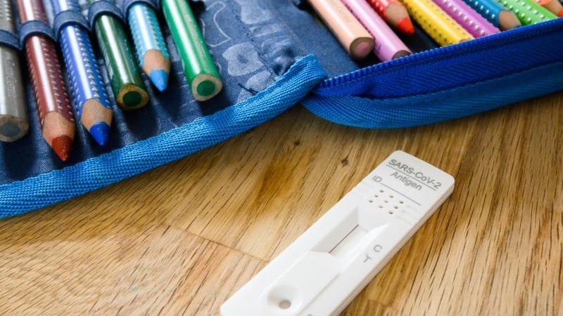 Ein Corona-Selbsttest liegt neben dem Etui eines Grundschülers. Foto: Julian Stratenschulte/dpa/Symbolbild