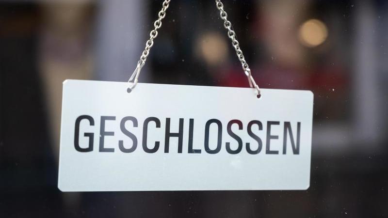 """In einem Schaufenster in der Fußgängerzone hängt ein Schild mit der Aufschrift """"geschlossen"""". Foto: Christophe Gateau/dpa/Symbolfoto"""