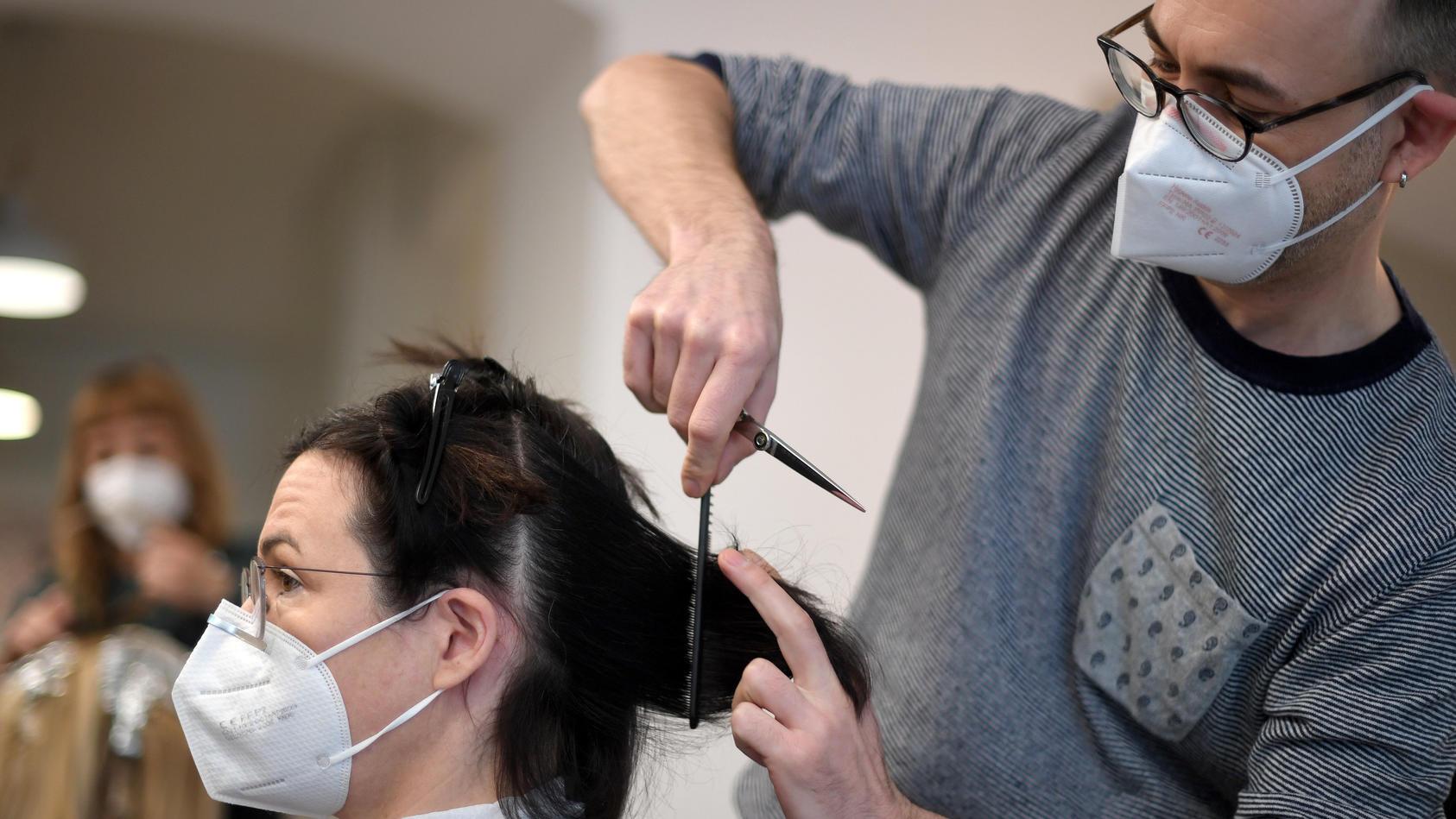 Friseur schneidet Frau die Haare.