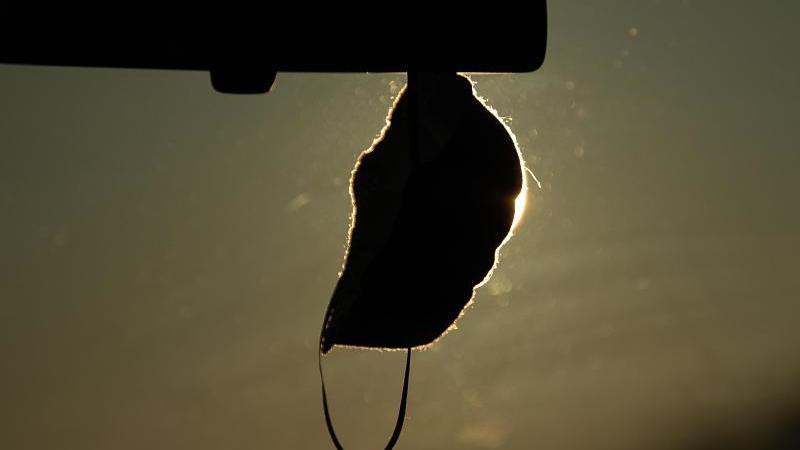 Eine FFP2-Maske hängt in einem Auto. Foto: Sebastian Gollnow/dpa/Symbolbild/Archivbild