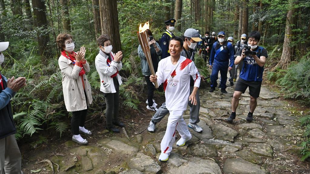 08.04.2021, Japan, Kihoku: Ein Mann läuft mit der Fackel beim Olympischen Fackellauf auf einem Bergpfad in der Präfektur Mie. Foto: --/kyodo/dpa +++ dpa-Bildfunk +++