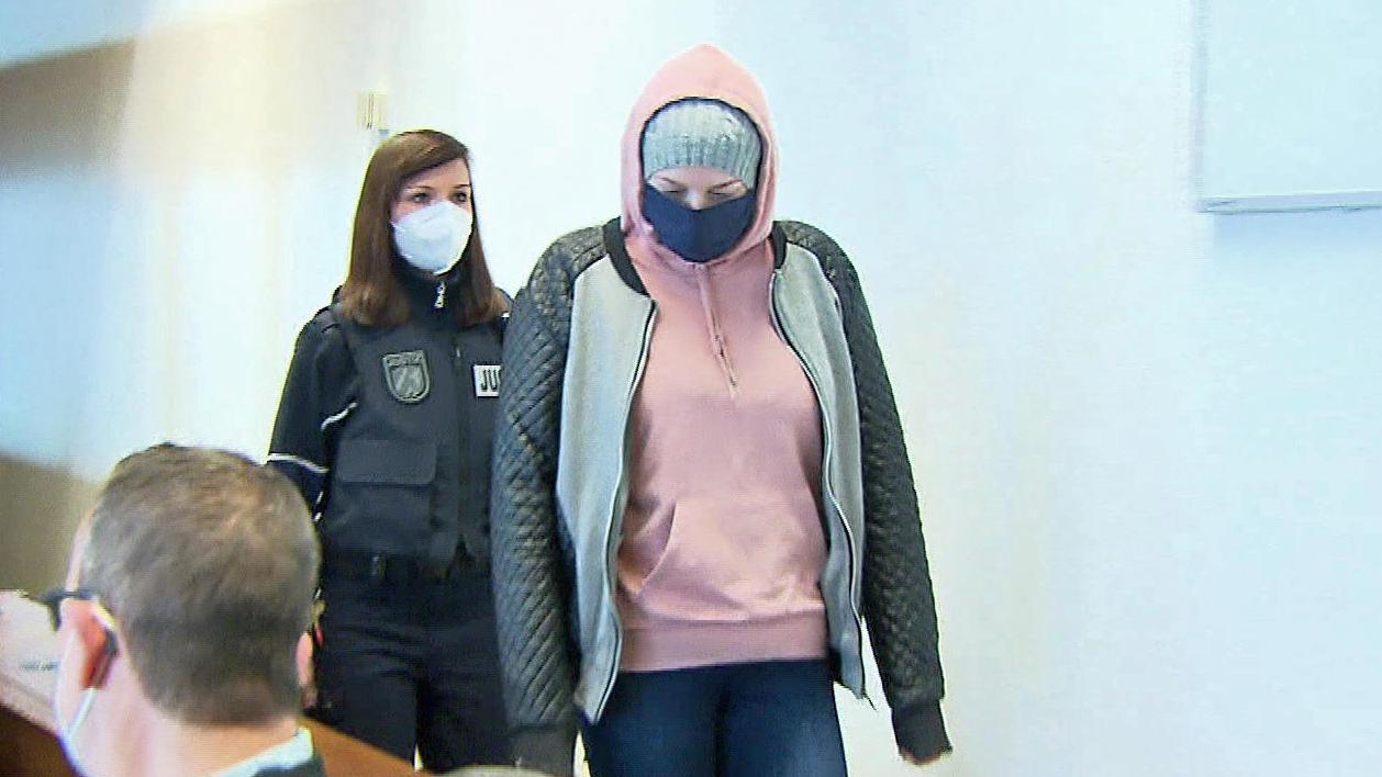 Eine Justizbeamtin bringt die Angeklagte (rechts) zum Prozessauftakt in das Kölner Landgericht