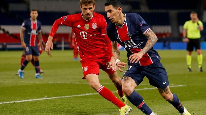 Münchens Thomas Müller (l) und Angel Di Maria von Paris kämpfen um den Ball. Foto: Sebastien Muylaert/dpa