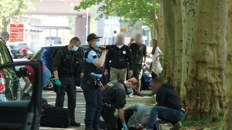 Polizisten betreuen einen verletzten Mann, der auf dem Weg zu einer Corona-Demo zusammengeschlagen wurde. Foto: Andreas Rosar/Andreas Rosar Fotoagentur-Stuttg/dpa/Archivbild