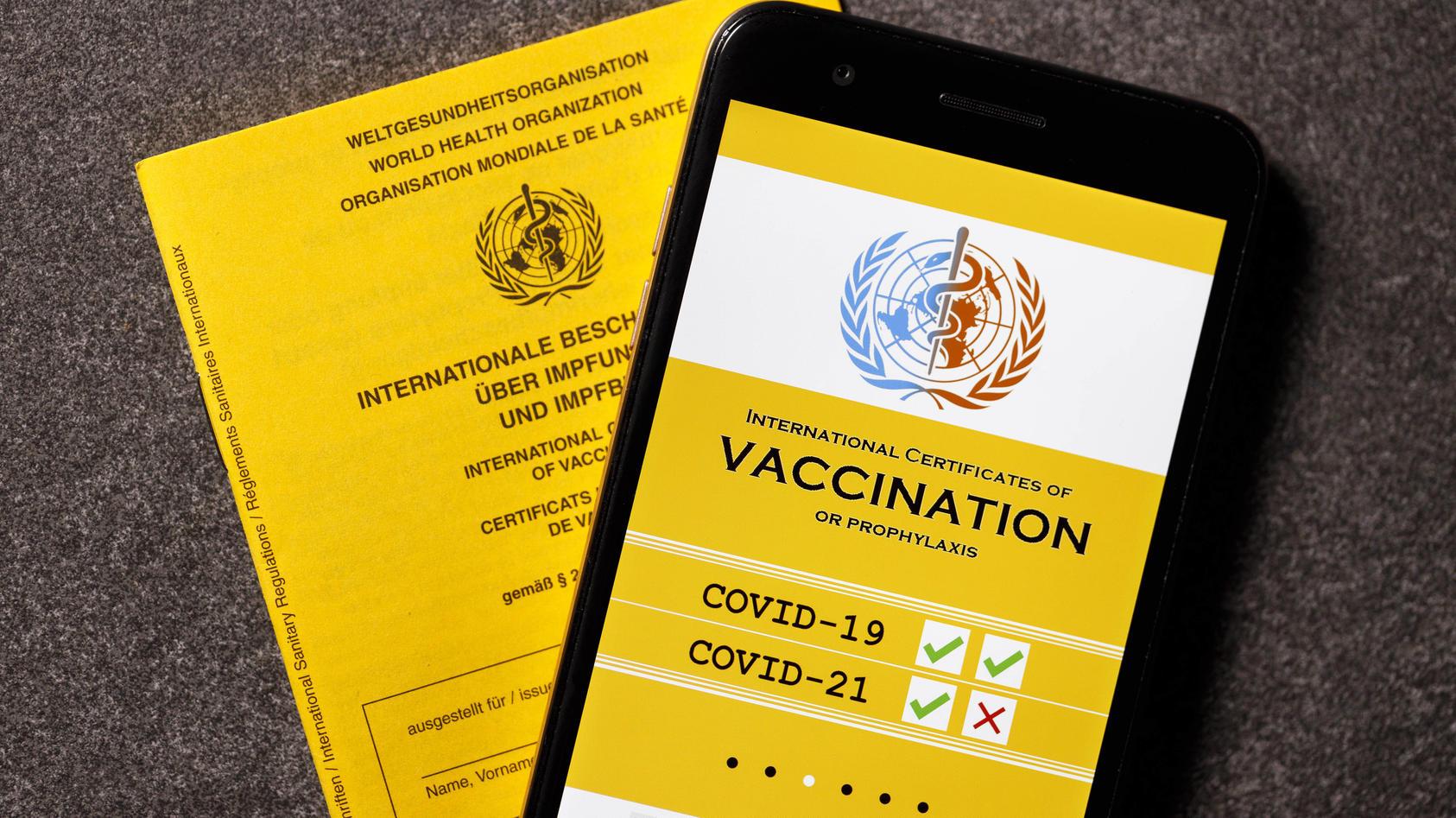 Eine mögliche Visualisierung des geplanten digitalen Impfpass liegt neben einem analogen Impfpass.