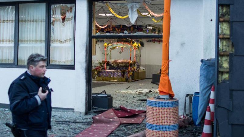 Ein Polizist geht nach der Explosion vor einem Essener Sikh-Tempel an der Eingangstür des Gebäudes vorbei. Foto: picture alliance/Marcel Kusch/dpa/Archivbild