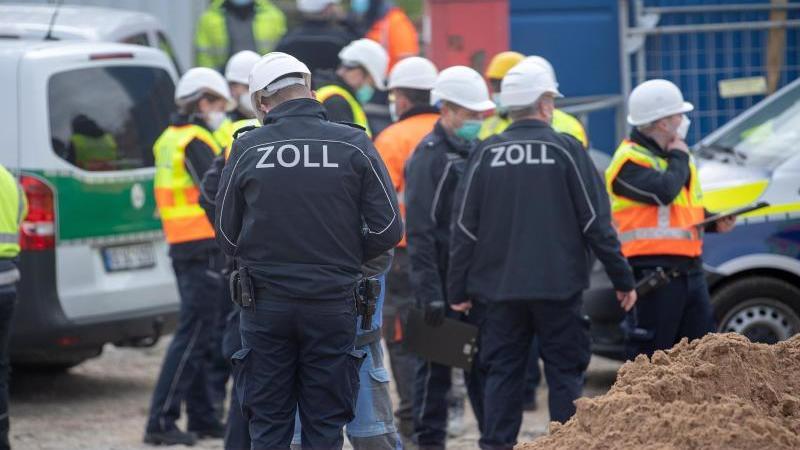 Mitarbeiter des Zolls führen auf einer Baustelle eine Durchsuchung im Zusammenhang mit Bekämpfung von Schwarzarbeit durch. Foto: Sebastian Gollnow/dpa/Aktuell