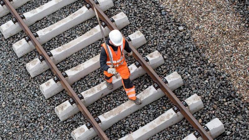 Ein Arbeiter geht über eine noch nicht fertige Gleisanlage der Bahn. Foto: Lukas Schulze/dpa/Symbolbild