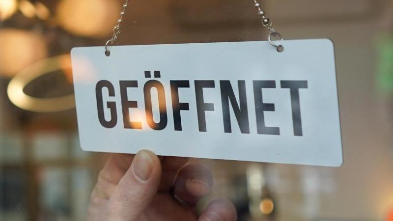 """Ein Wendeschild mit der Aufschrift """"geöffnet"""" wird umgedreht. Foto: Jörg Carstensen/dpa/Symbolbild"""