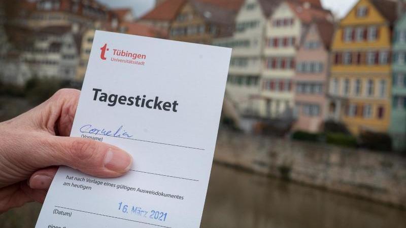 """Eine Frau zeigt am Neckar ihr """"Tagesticket"""", das aufgrund eines negativen Testergebnis bei einem Corona-Schnelltest ausgestellt wurde. Foto: Sebastian Gollnow/dpa/Archivbild"""