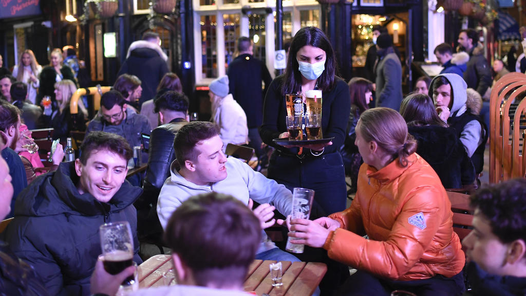 A waitress serves drinks as customers sit at setup tables outside pubs in Soho, in London, on the day some of England's third coronavirus lockdown restrictions were eased by the British government, Monday, April 12, 2021. People across England flocke