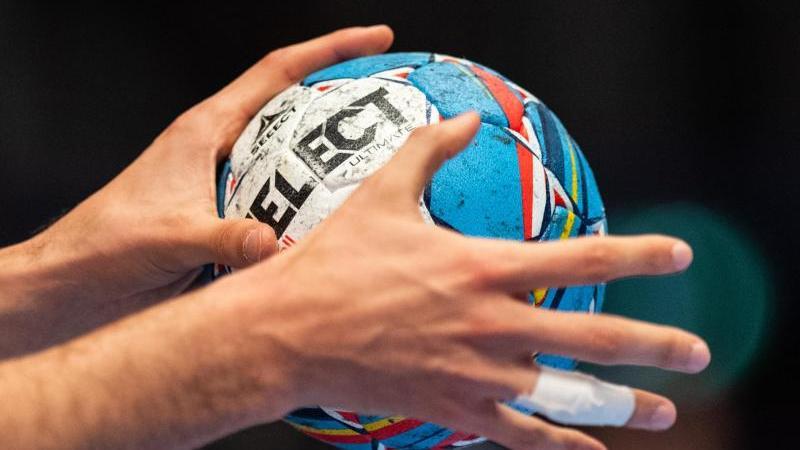 Ein Handballer hält einen Handball in den Händen. Foto: Robert Michael/dpa/Symbolbild