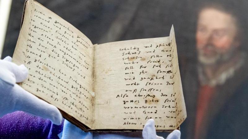 Eine Handschrift des Reformators Philipp Melanchthon vor einemPorträt, das Melanchthon darstellt. Foto: Hendrik Schmidt/dpa-Zentralbild/dpa/Archivbild
