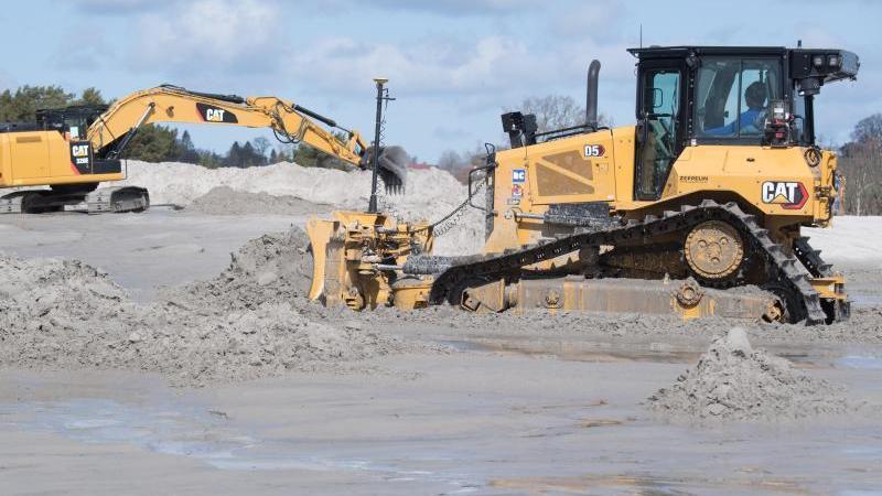 Planierraupen und Bagger verteilen den aufgespülten Sand am Ostseestrand. Foto: Stefan Sauer/dpa/Archivbild