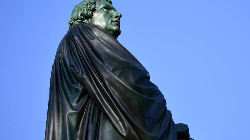 Eine Figur des Reformators Martin Luther aus Bronze steht als Teil des Luther-Denkmals im Heylshofpark. Foto: picture alliance / Uwe Anspach/dpa/Archivbild